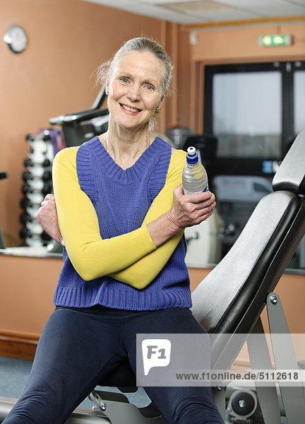 Ältere Frau trinkt Wasser im Fitnessstudio