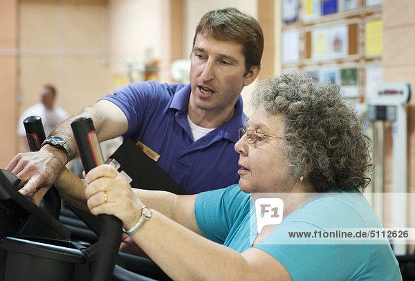 Trainerin hilft älteren Frauen beim Training