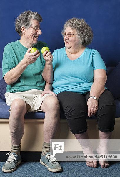Das ältere Paar isst zusammen Äpfel.