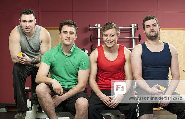 Men sitting together in gym