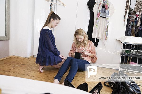 Teenage girls sitting in bedroom