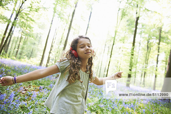 Girl listening to headphones in forest