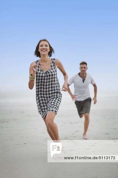 Ein Paar jagt sich gegenseitig am Strand.