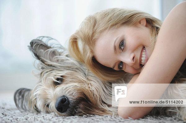Lächelnde Frau umarmt Hund zu Hause