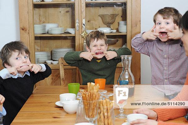 Jungen machen Gesichter bei Tisch