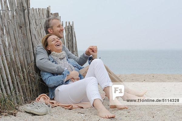 Ältere Paare umarmen sich am Strand