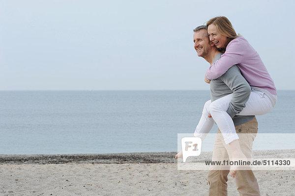 Mann mit Freundin am Strand