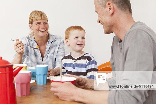 Familie lacht beim Frühstück
