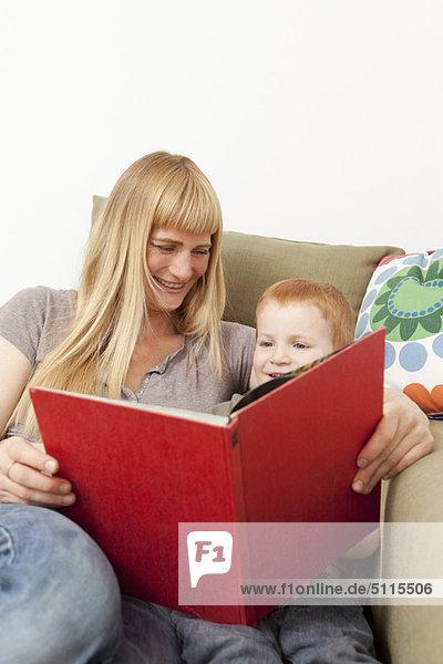 Mutter und Sohn beim gemeinsamen Lesen auf dem Sofa
