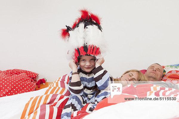 Junge mit Kriegshaube im Bett der Eltern
