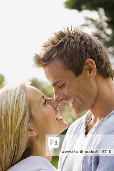 Lächelndes Paar berührt Nasen im Freien