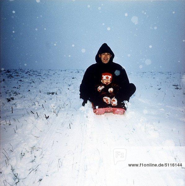 Vater und Kind Pulkariding im Schnee
