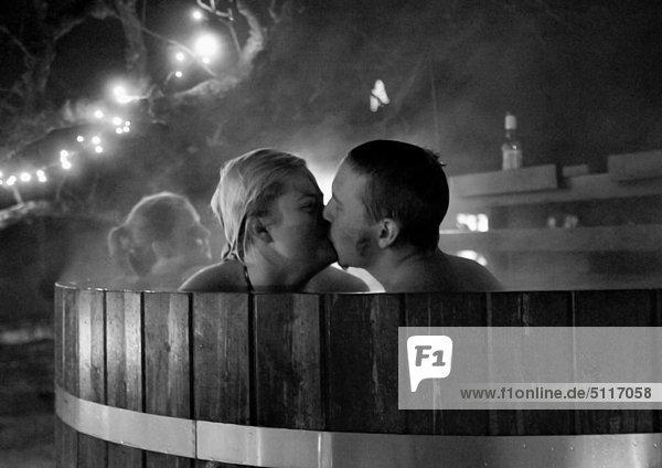 Ein junges paar küssen im Fass Baden