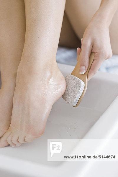 woman using feet pumice