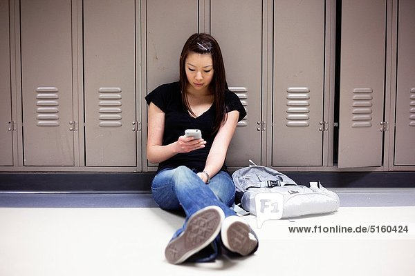 Young Asian woman texting on her smart phone while sitting on floor in school hallway.