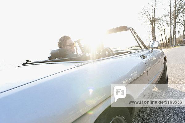 Mittelgroßer Mann fährt Oldtimer an der Elbe