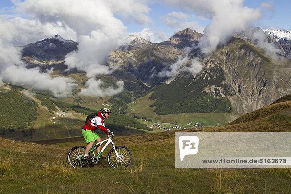 Italy  Livigno  View of woman riding mountain bike