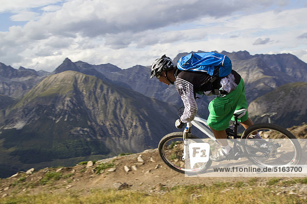Italy  Livigno  View of man riding mountain bike downhill