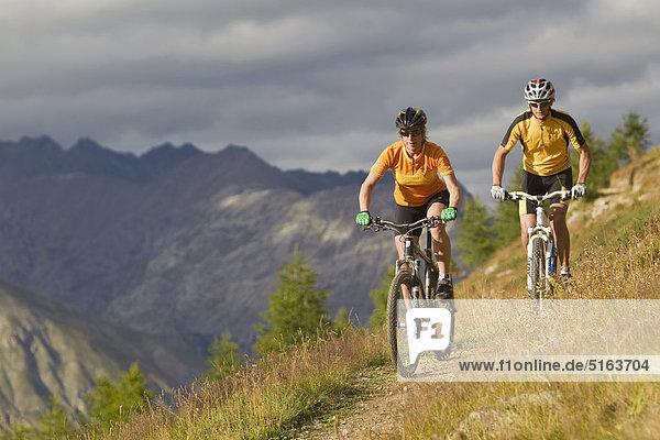 Italien  Livigno  Blick auf Mann und Frau beim Mountainbiken