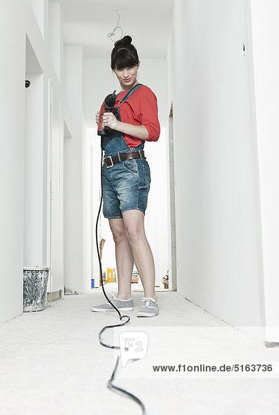 Junge Frau mit Elektrobohrer zur Renovierung im Flur