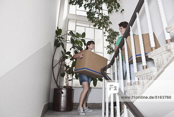 Deutschland  Köln  Junges Paar mit Karton auf der Treppe in renovierter Wohnung