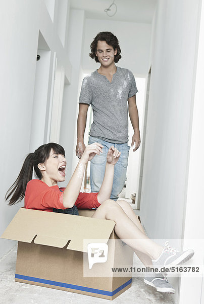 Young woman inside carton and man standing beside in renovating apartment