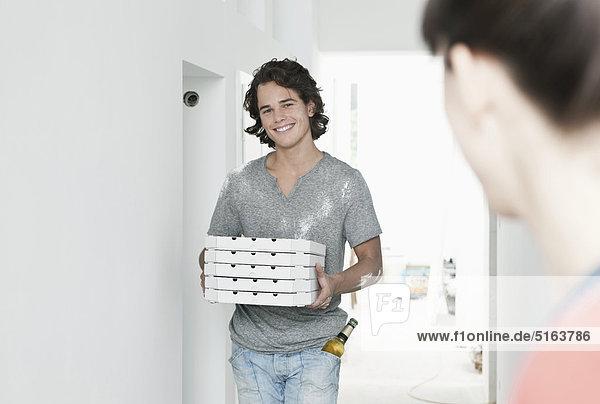 Junger Mann mit Pizzakarton in renovierter Wohnung
