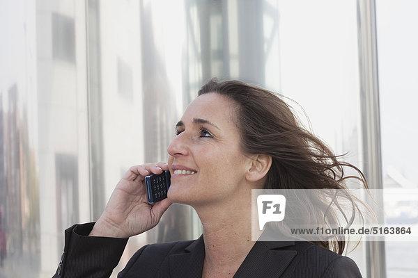 Nahaufnahme einer Geschäftsfrau mit windgepeitschten Haaren am Handy