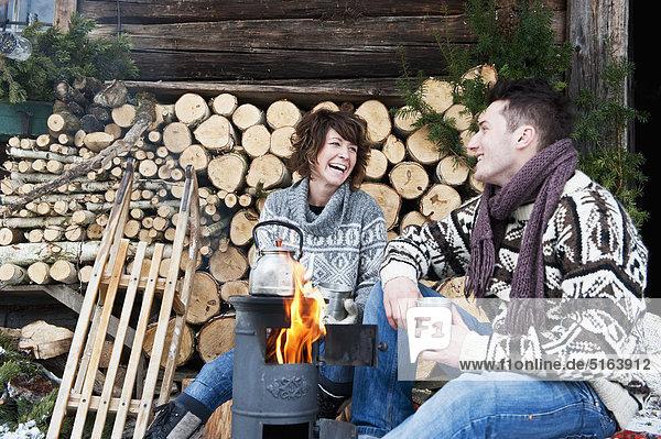 Österreich  Salzburger Land  Flachau  Junger Mann und Frau machen Tee und sitzen im Winter neben dem Herd.
