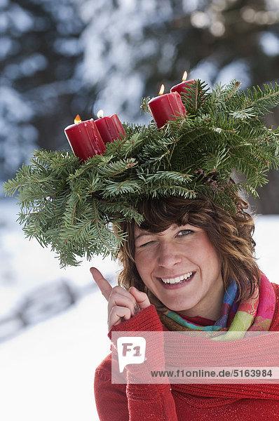 Österreich  Salzburger Land  Flachau  Nahaufnahme einer jungen Frau mit Adventskranz auf dem Kopf im Winter