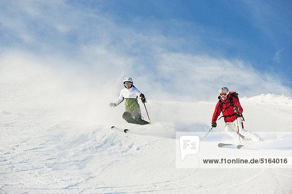 Österreich  Salzburger Land  Altenmarkt-Zauchensee  Mittelalterliches Paar Skifahren auf der Piste im Winter