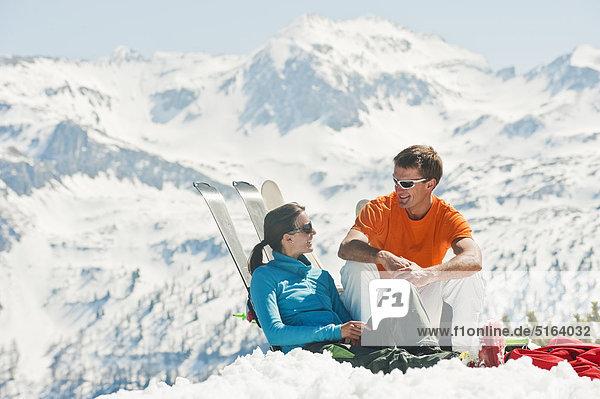 Österreich  Salzburger Land  Altenmarkt-Zauchensee  Mittelalterliches Paar im Winter auf Skiern sitzend und lehnend