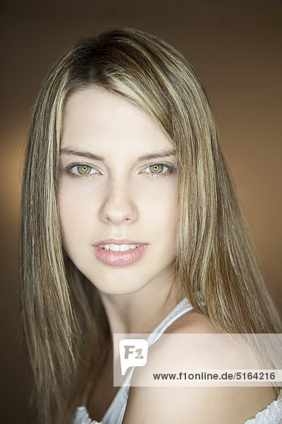 Nahaufnahme einer jungen Frau vor braunem Hintergrund  lächelnd  Porträt