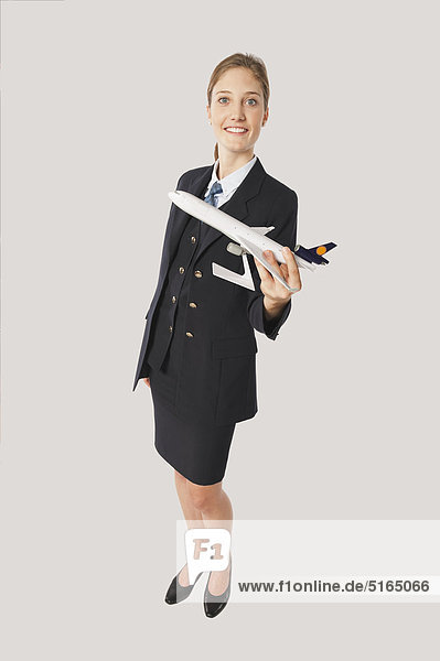 Junge Flugbegleiterin mit Modellflugzeug vor weißem Hintergrund  lächelnd  Portrait