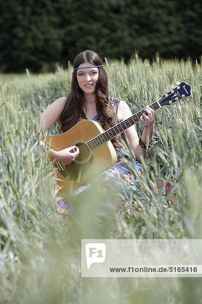 Junge Frau mit Gitarre im Kornfeld