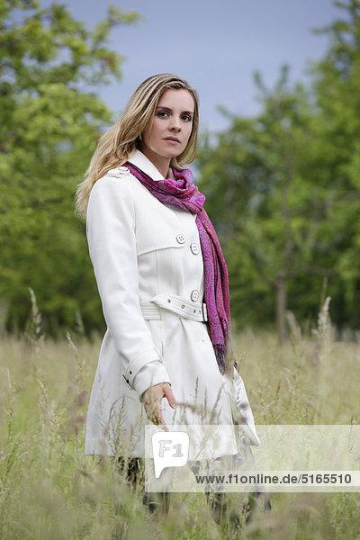 Junge Frau in weißem Trenchcoat