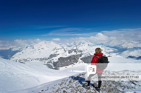 A women hiking in high snow covered mountains looks at view