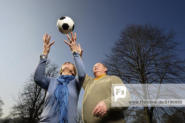 Älteres Paar spielt mit Fußball
