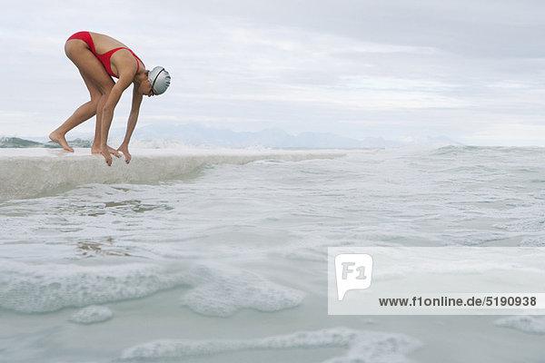 Läufer springt vom Dock ins Wasser