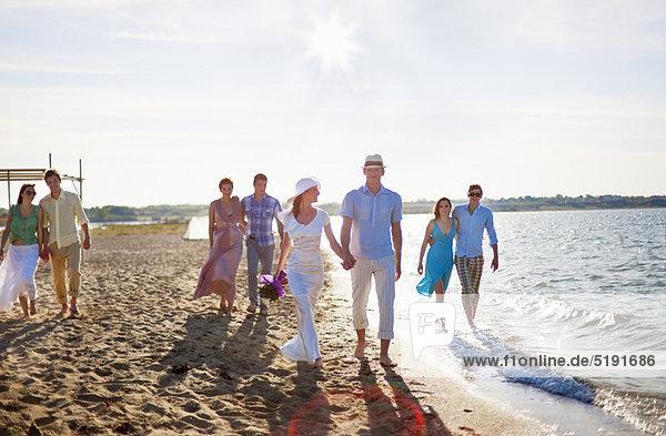 Neuvermähltes Paar am Strand mit Freunden