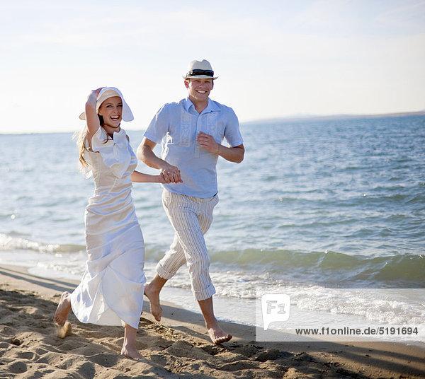Neuvermähltes Paar am Strand unterwegs