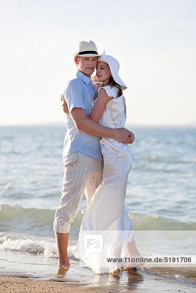 Neuvermähltes Paar umarmt am Strand