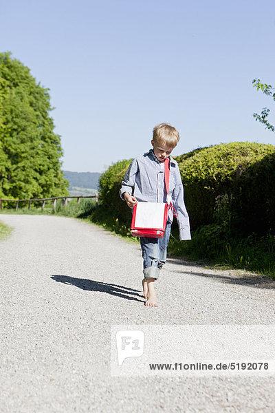 Junge  der barfuß auf der Landstraße läuft