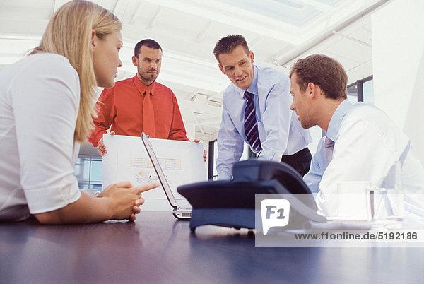 Geschäftsleute  die gemeinsam am Schreibtisch arbeiten