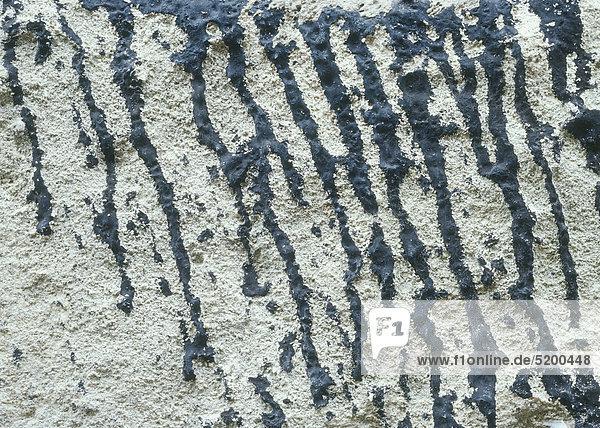 Dunkelblaue Farbspritzer an weißem Wandputz