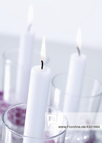 Drei brennende Kerzen in Gläsern