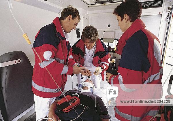 Notarzt und Rettungssanitäter mit Patient im Rettungswagen