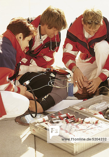 Notarzt und Rettungssanitäter mit Patient am Boden