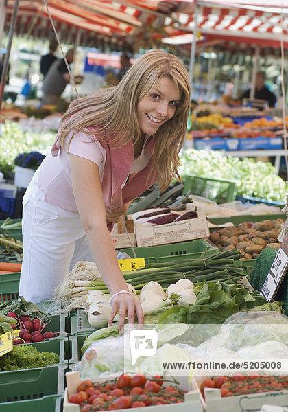 Junge Frau beim Gemüsestand am Markt