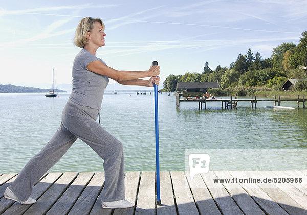 Ältere Frau bei Stretching-Übung mit Stock auf Steg an See